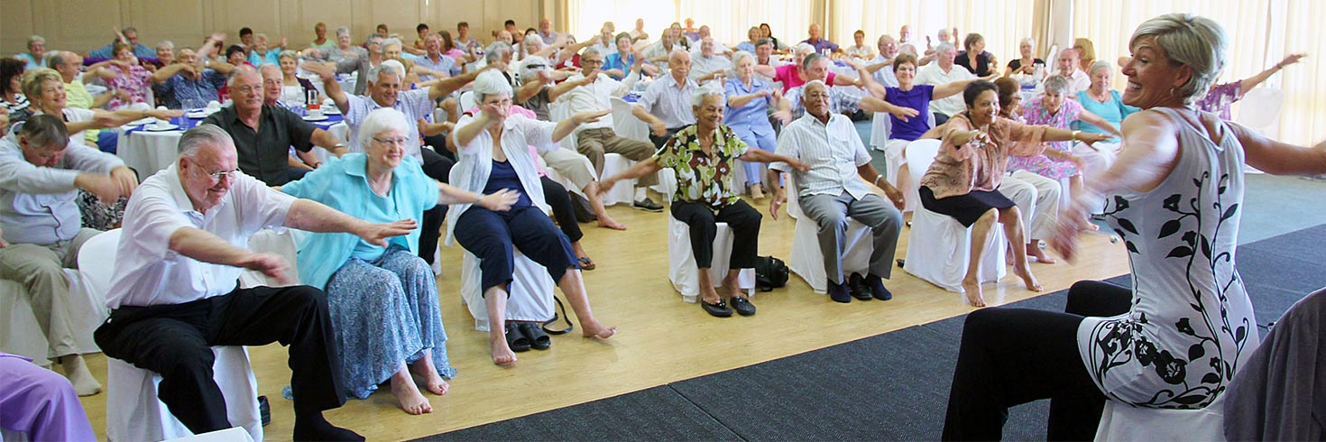 A room full of elderly patients taking an exercise class